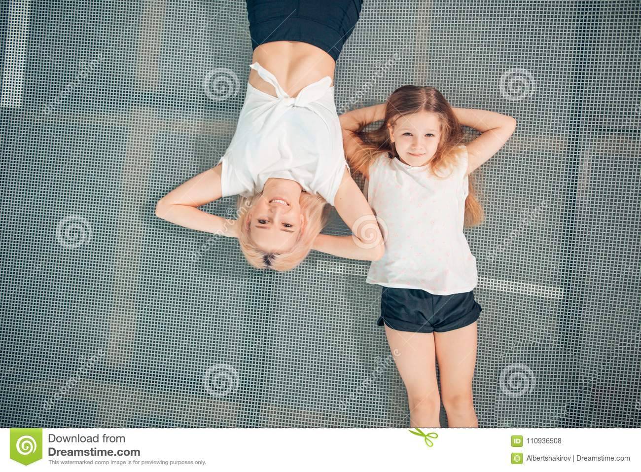 Mother and little daughter playing at playground and lying on trampoline