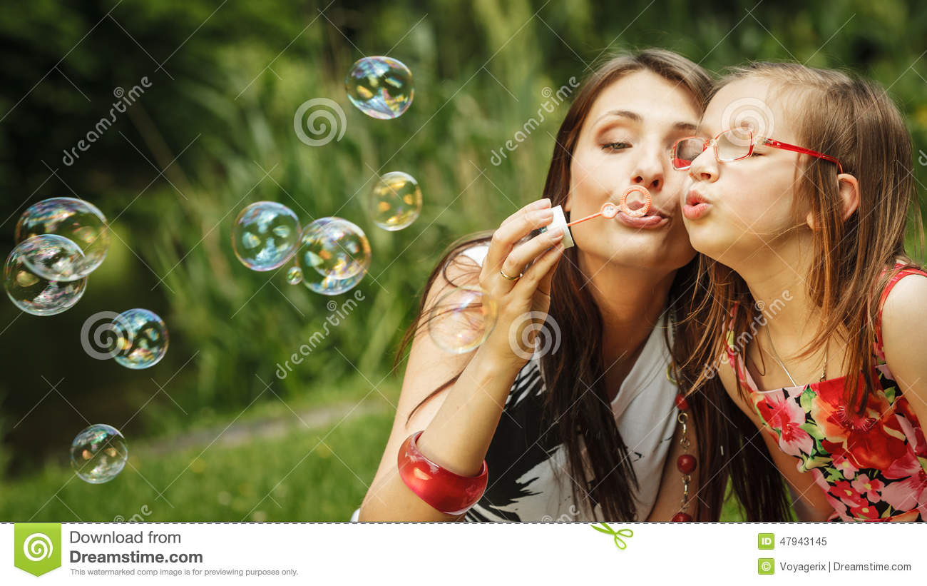 Mother And Little Girl Blowing Soap Bubbles In Park. Stock