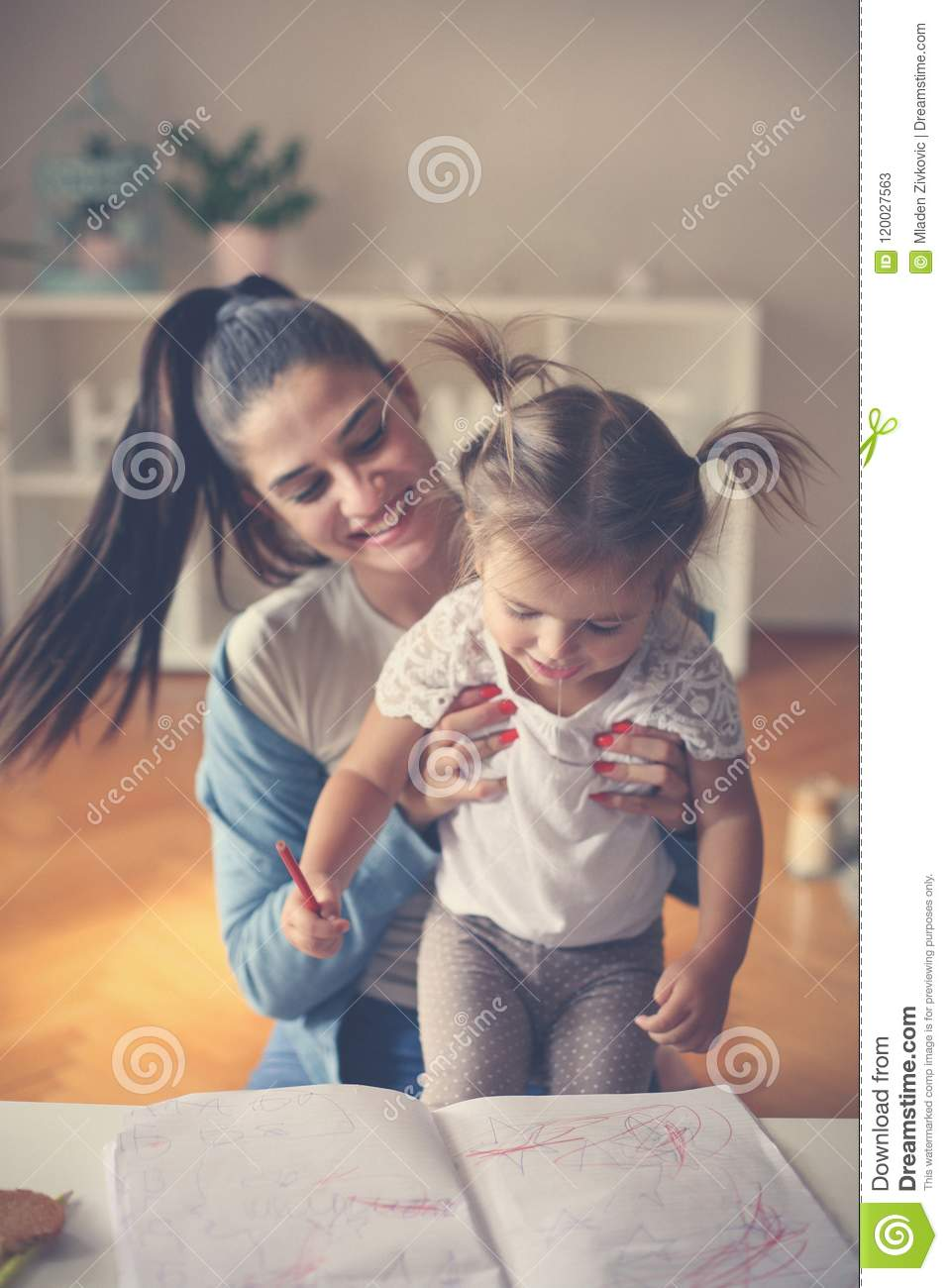 Mother and little girl at home playing and reading.