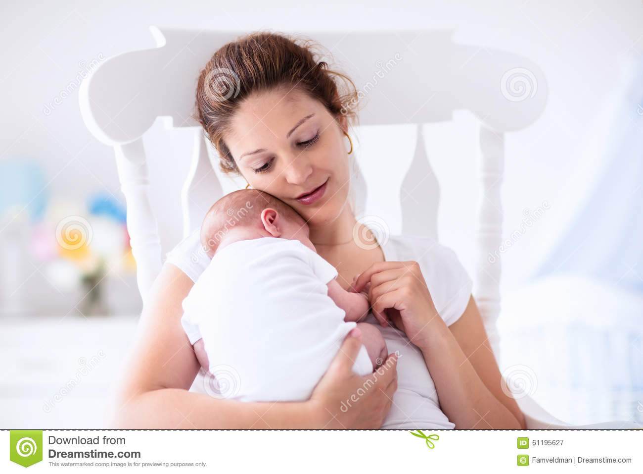 mother and newborn baby in white nursery stock image