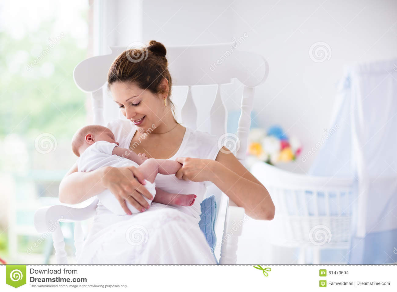 Blue nursery rocking chair - Mother And Newborn Baby In White Nursery Stock Photo