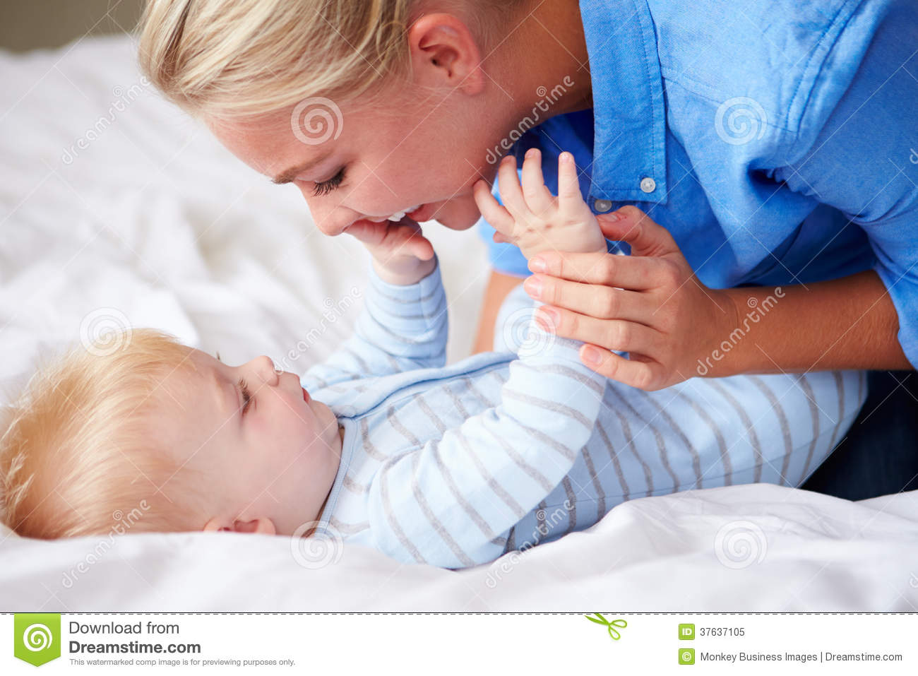 mother playing with baby son as they lie in bed together royalty free stock photo image 37637105. Black Bedroom Furniture Sets. Home Design Ideas