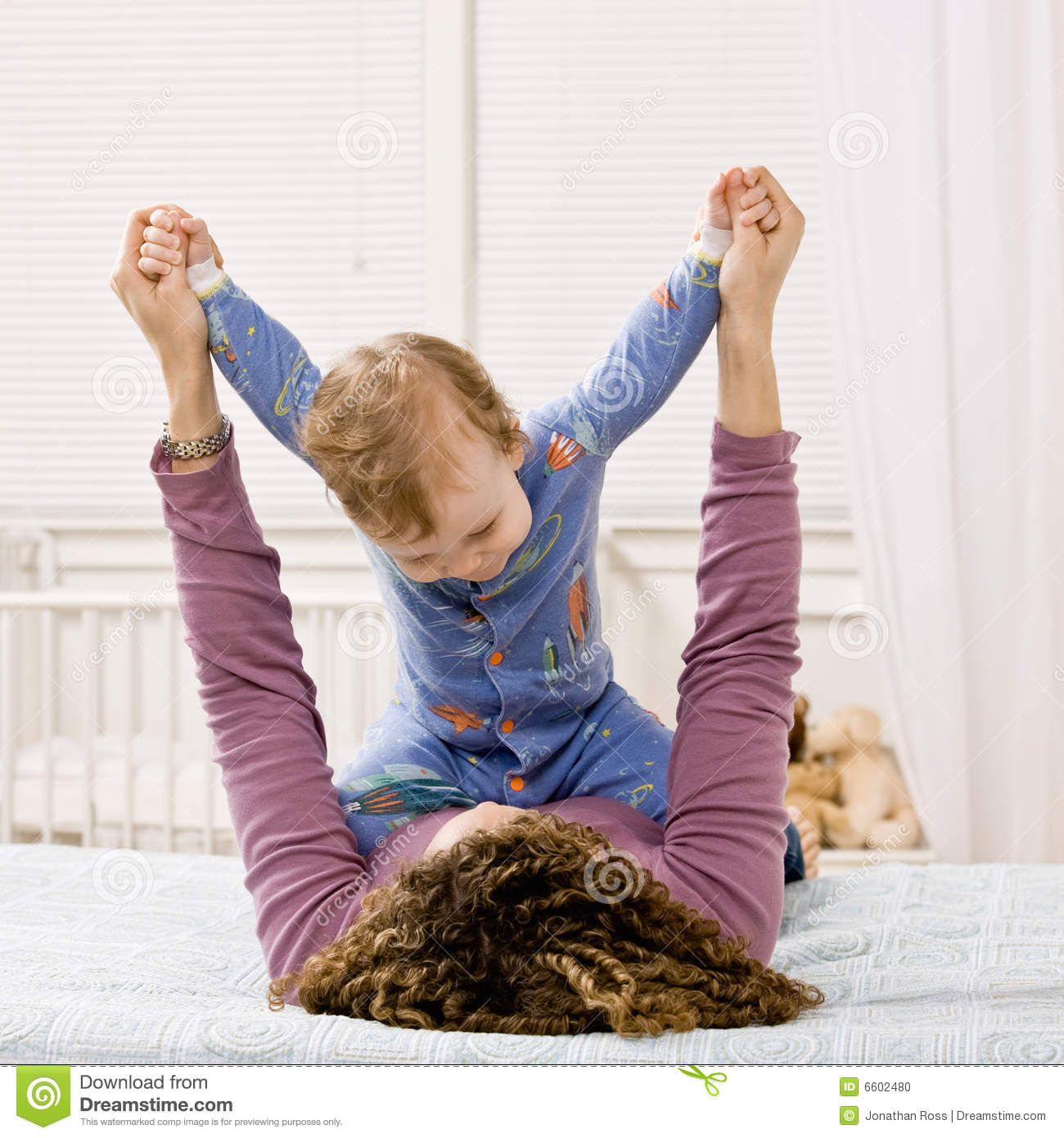mother playing with son on bed in bedroom stock photo