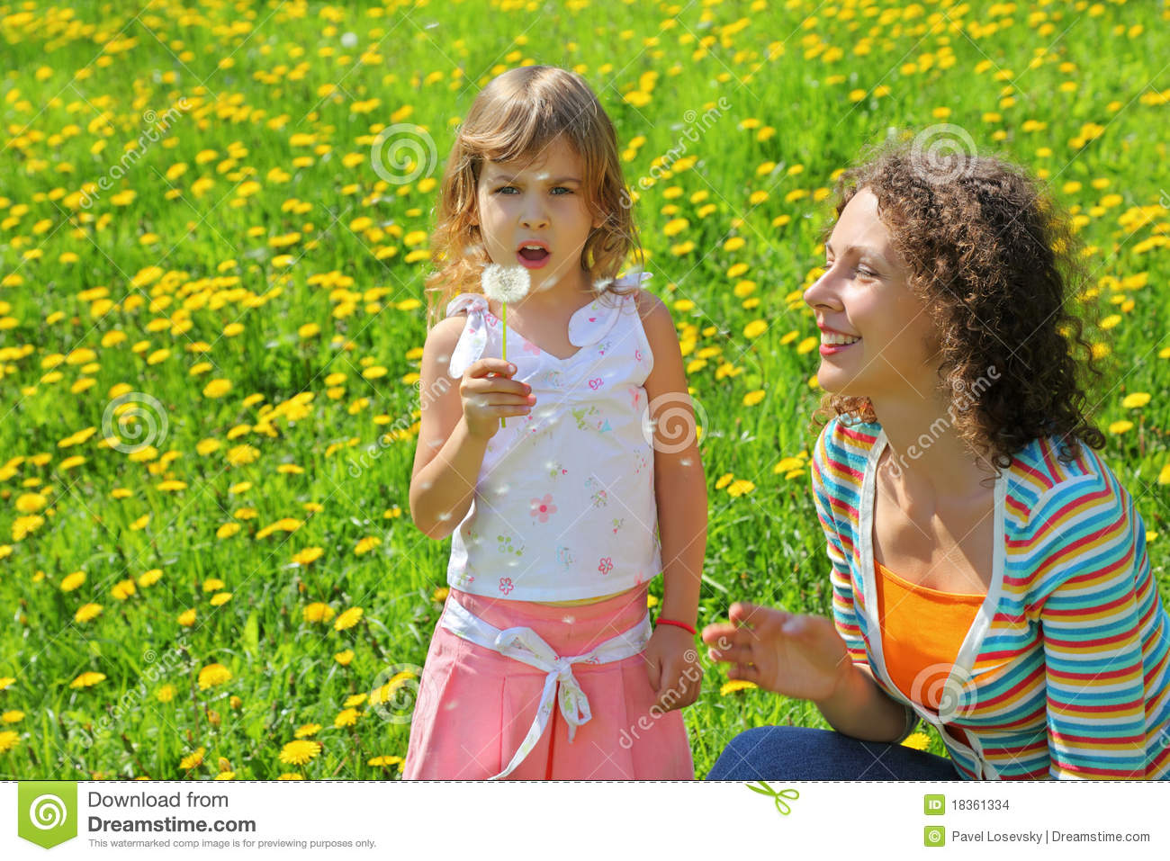 Mother plays with girl which breath on dandelion
