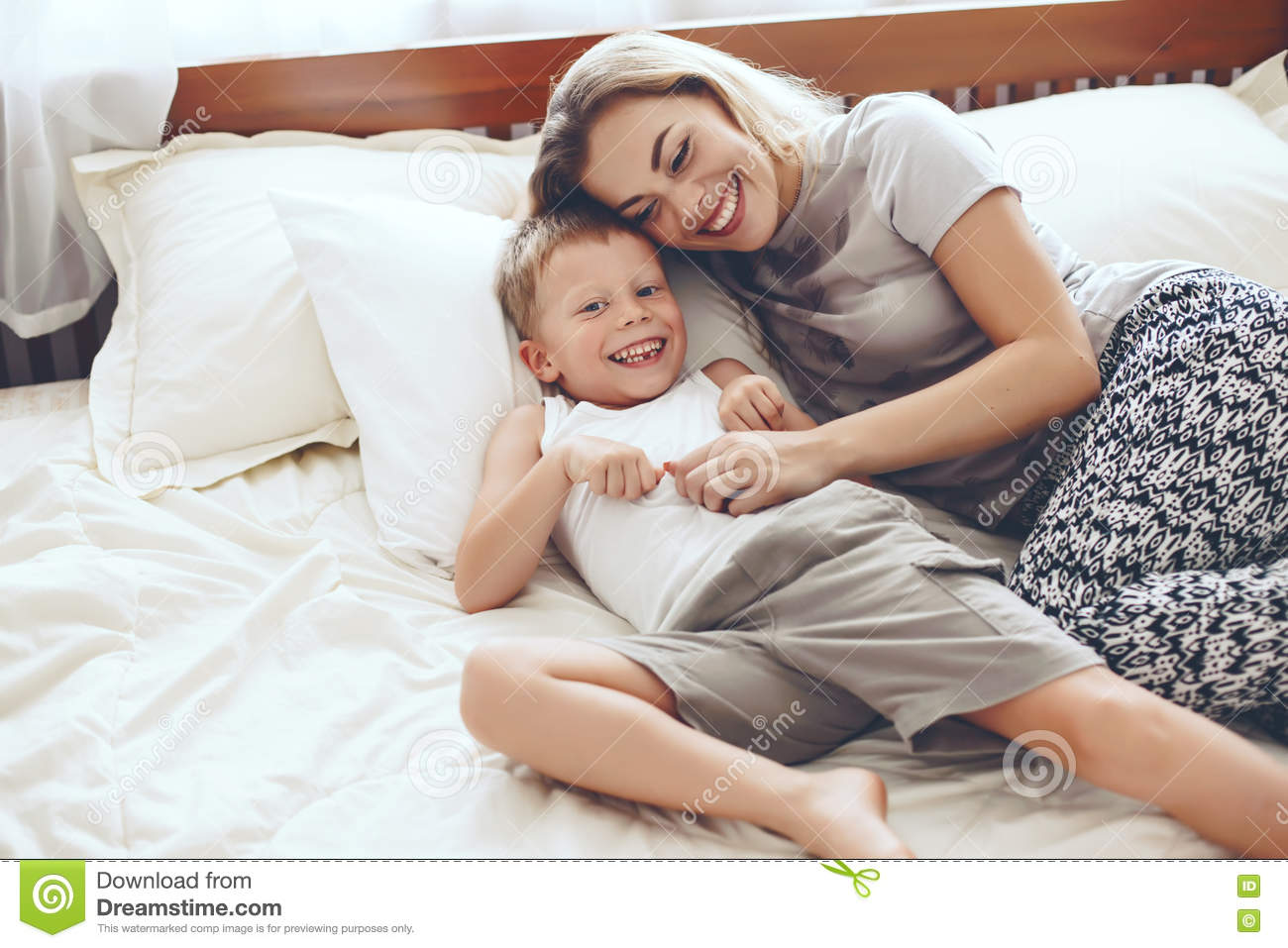 mother plays with son in bed stock photo image 70399722. Black Bedroom Furniture Sets. Home Design Ideas