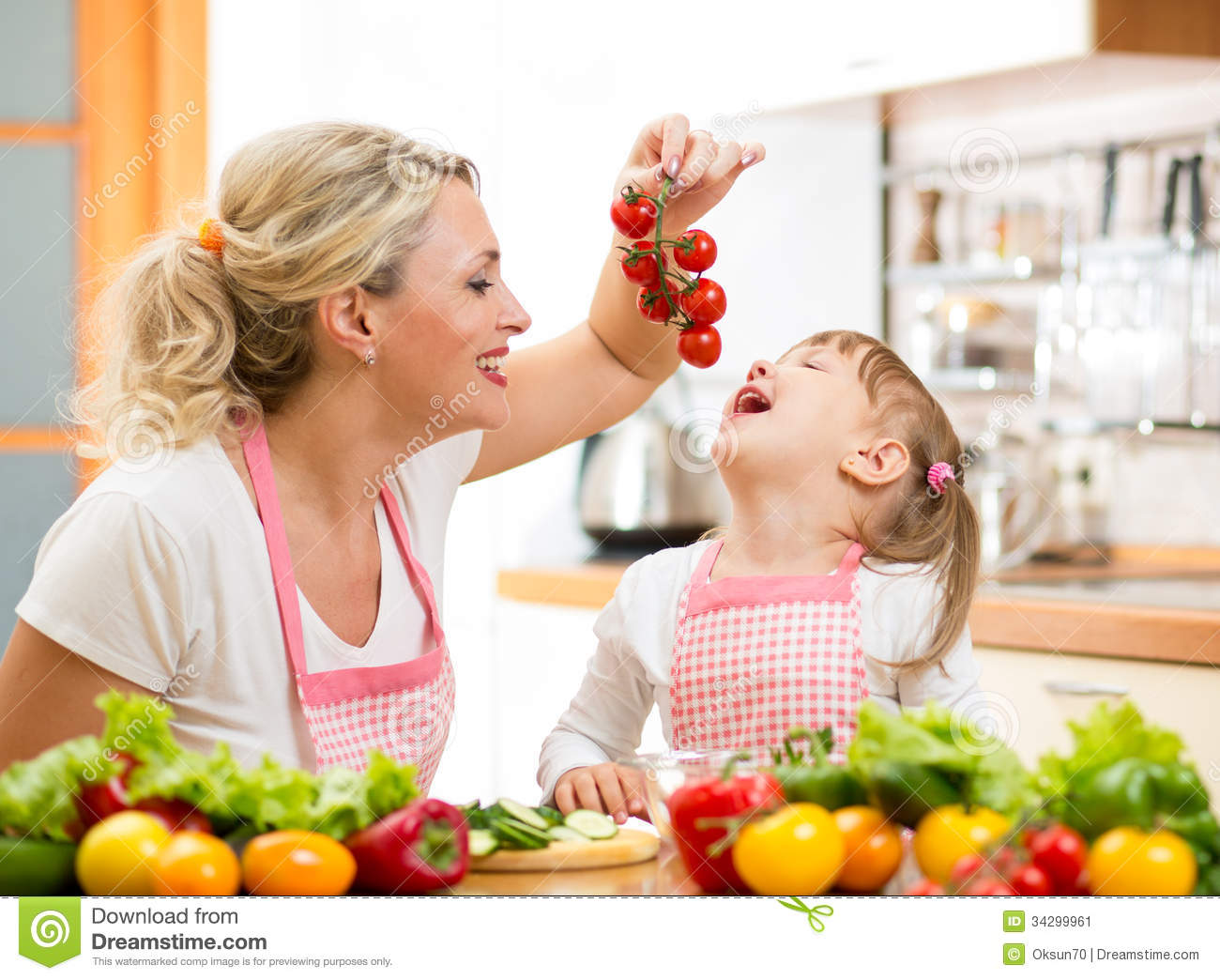 Mother Preparing Dinner And Feeding Kid Tomatoes In Kitchen Stock