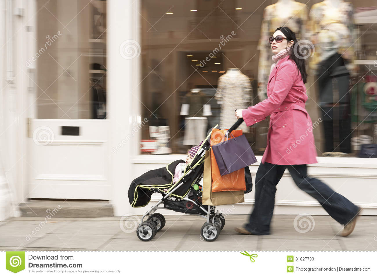 Mother Pushing Stroller By Clothes Shop Stock Photo - Image: 31827790
