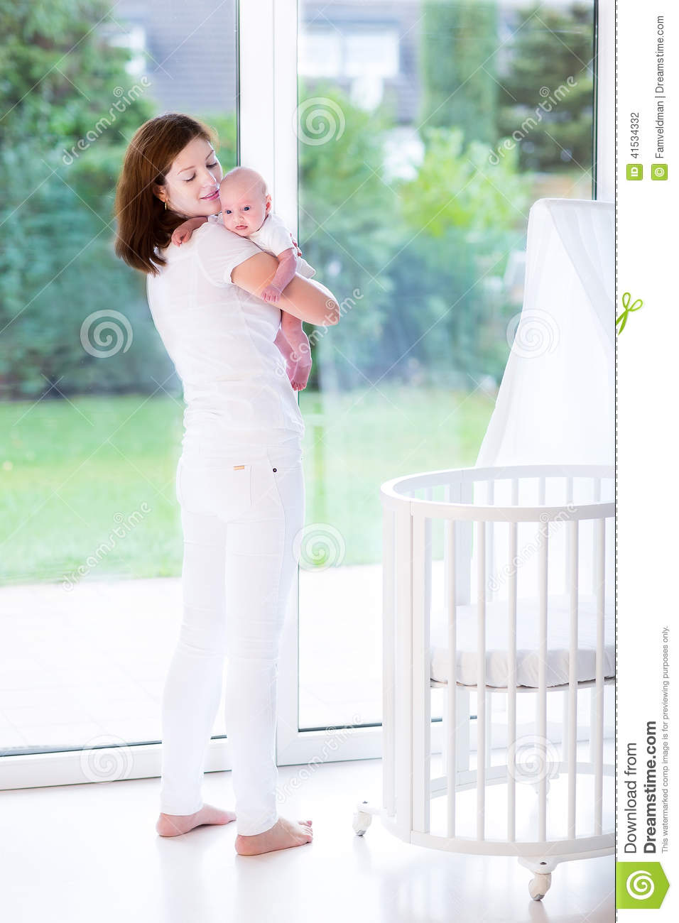 Baby bed next to bed - Mother Putting Newborn Baby In Bed Next To Window