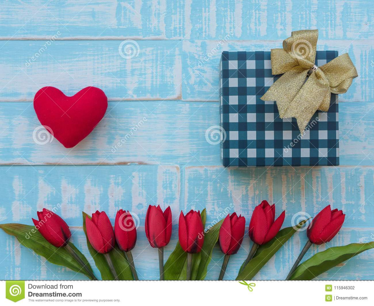 Mother`s day concept. red heart, tulips flower and giftbox on p