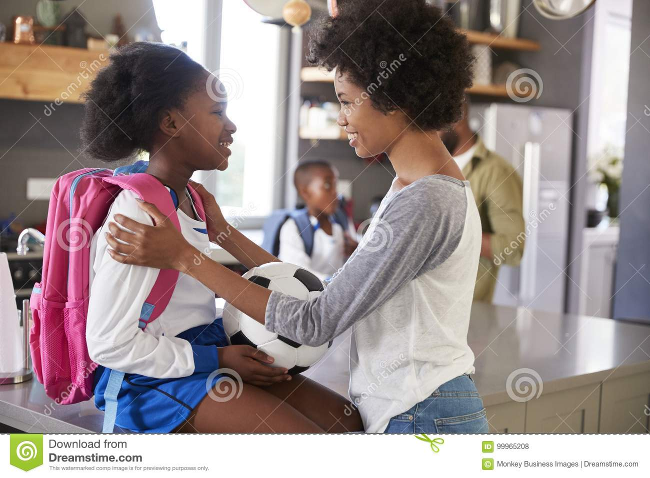 Mother Saying Goodbye To Daughter As She Leaves For School