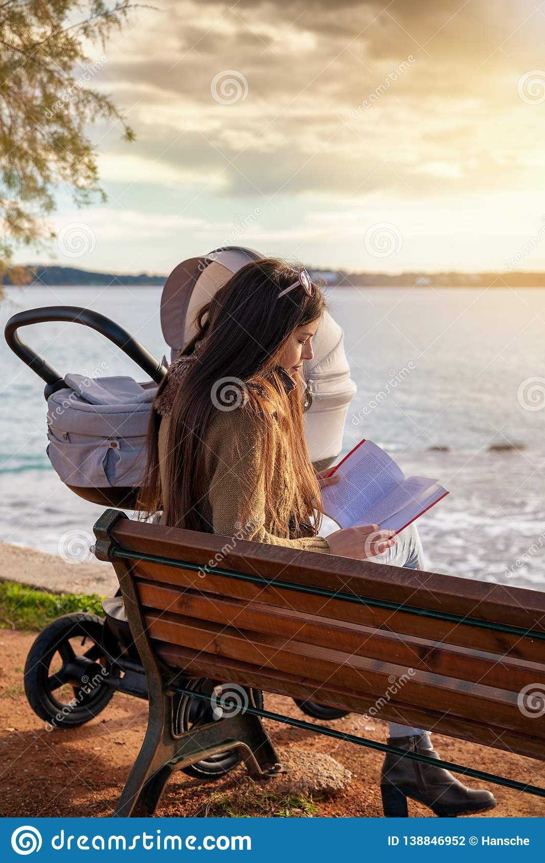Mother sits on a bench at the sea with her baby and reading a book