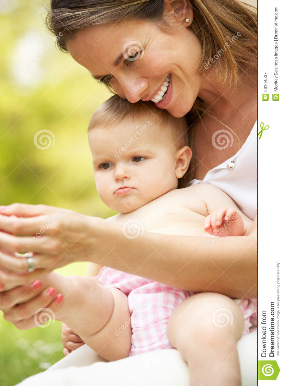Mother Sitting With Baby Girl In Field