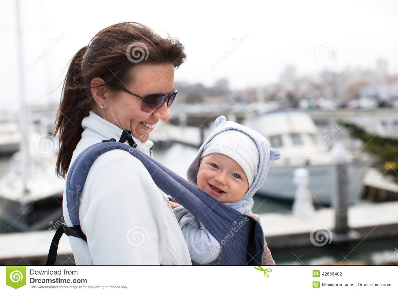 e881d107fdf Mother And A Smiling Cute Baby Boy In A Baby Carrier Stock Photo ...