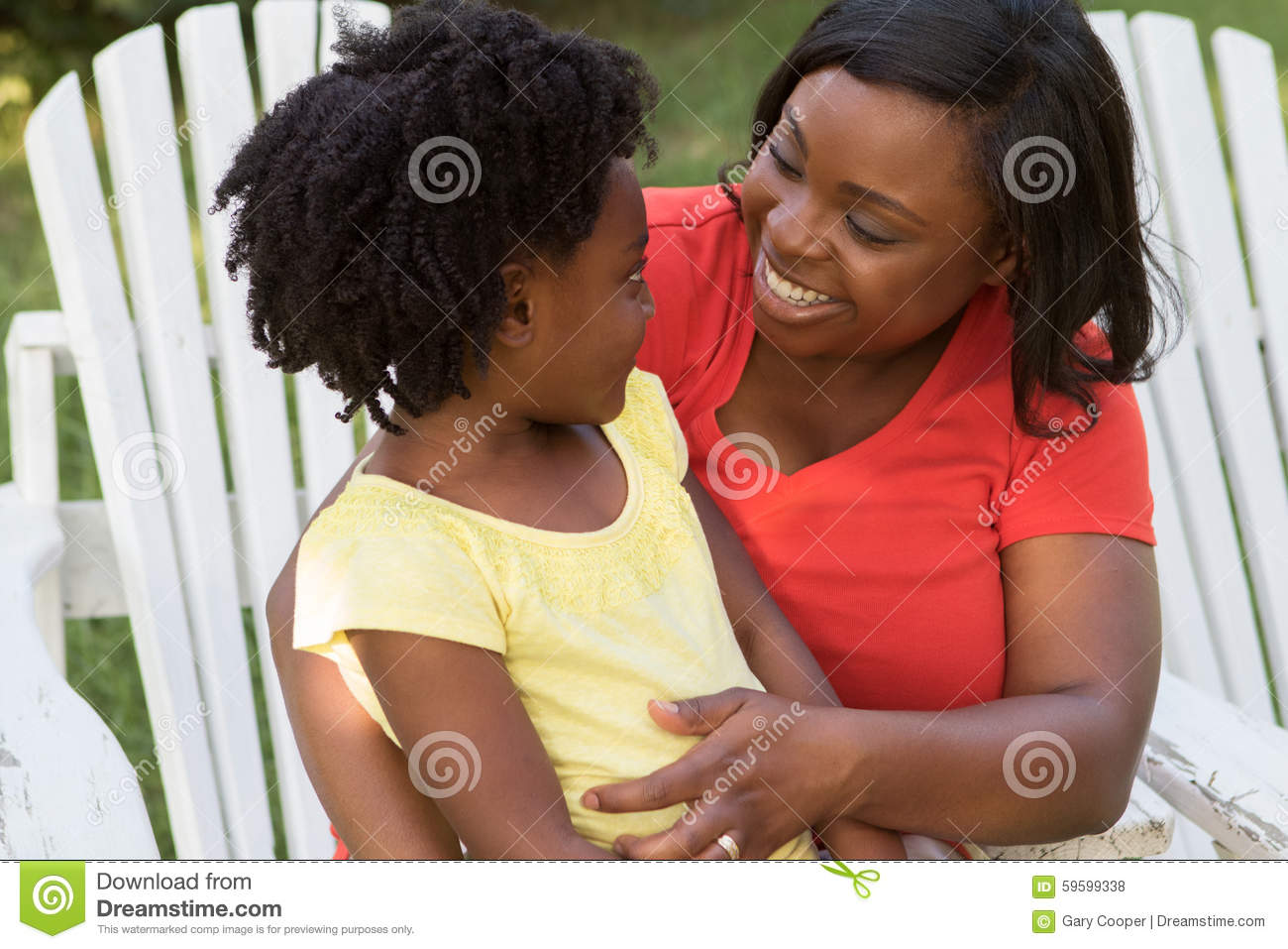 Mother Smiling And Talking With Her Daughter Stock Photo