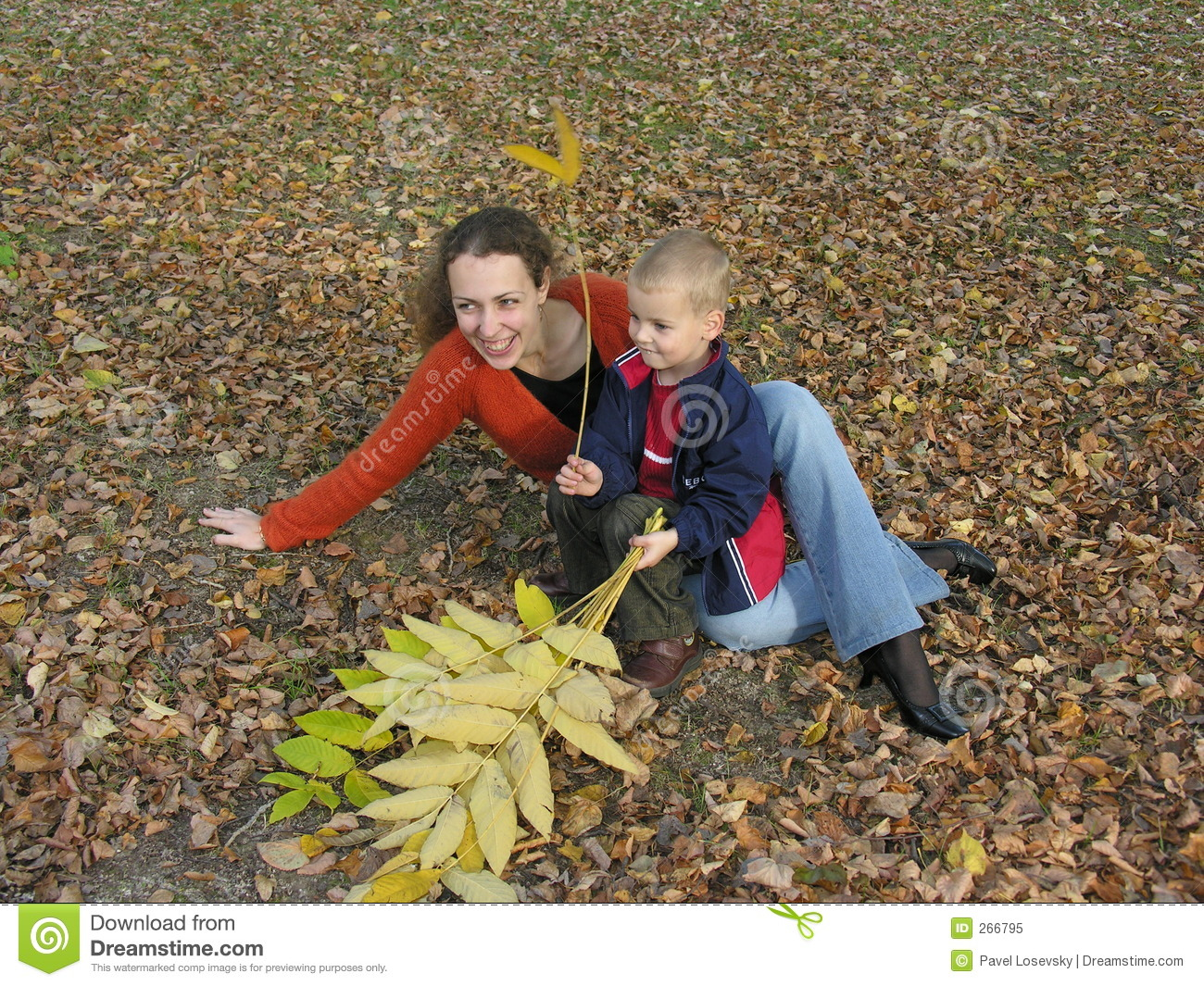 Mother with son with autumn leaves