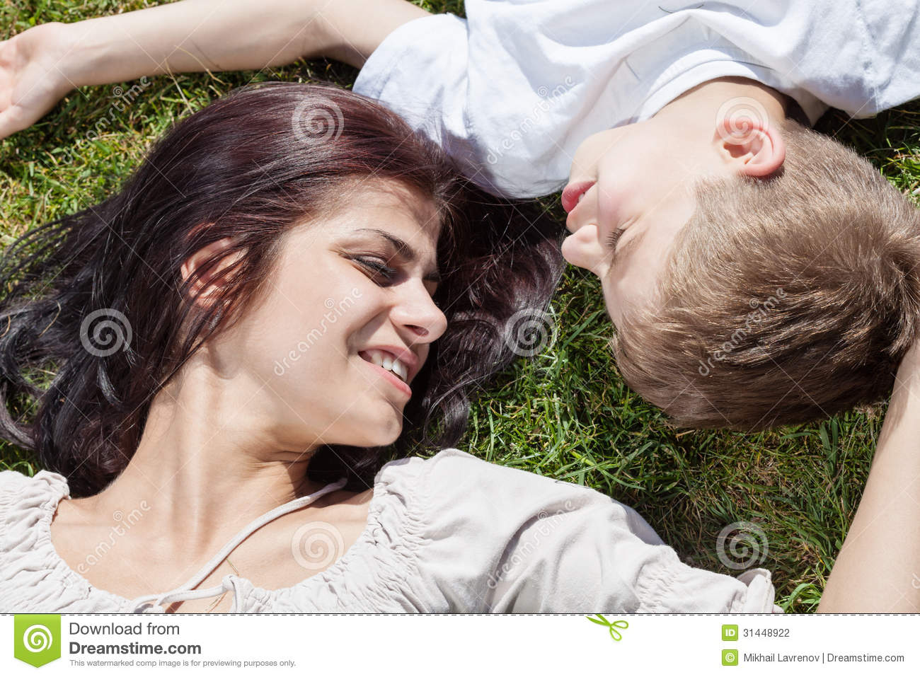 Mother and son lying on the grass head to head