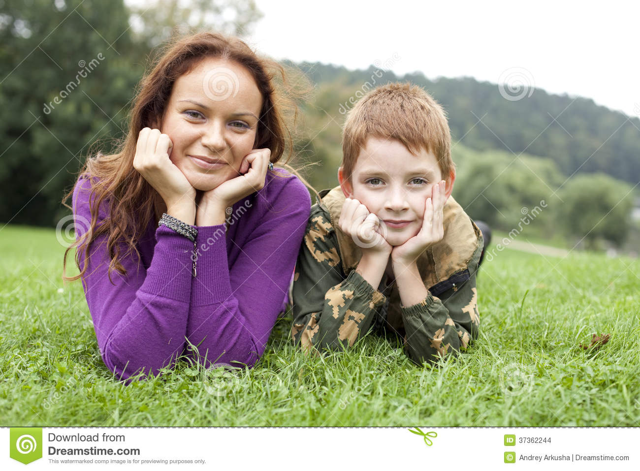 Mother and son lying on the green grass