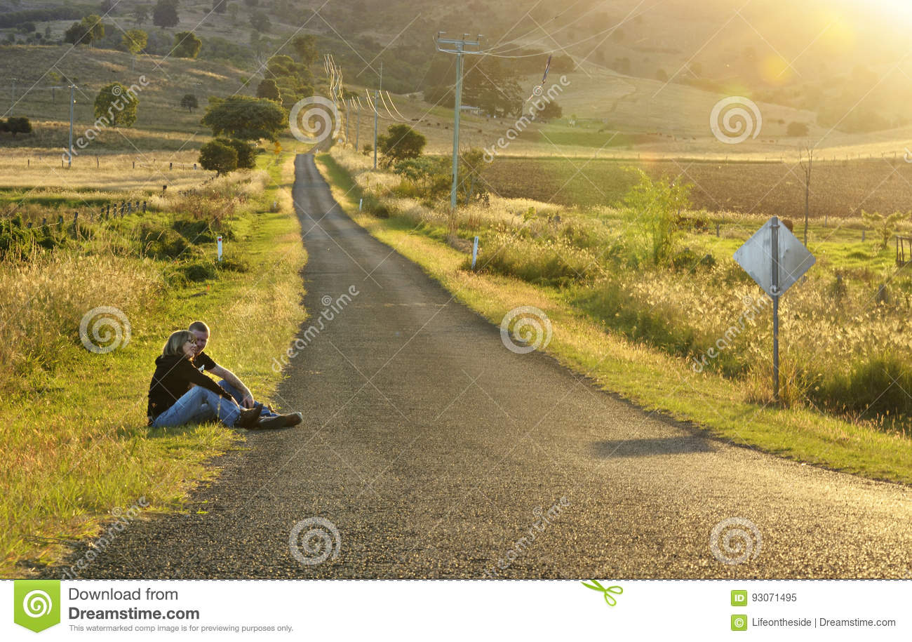 Mother and son sitting by long empty country road watching sunset countryside