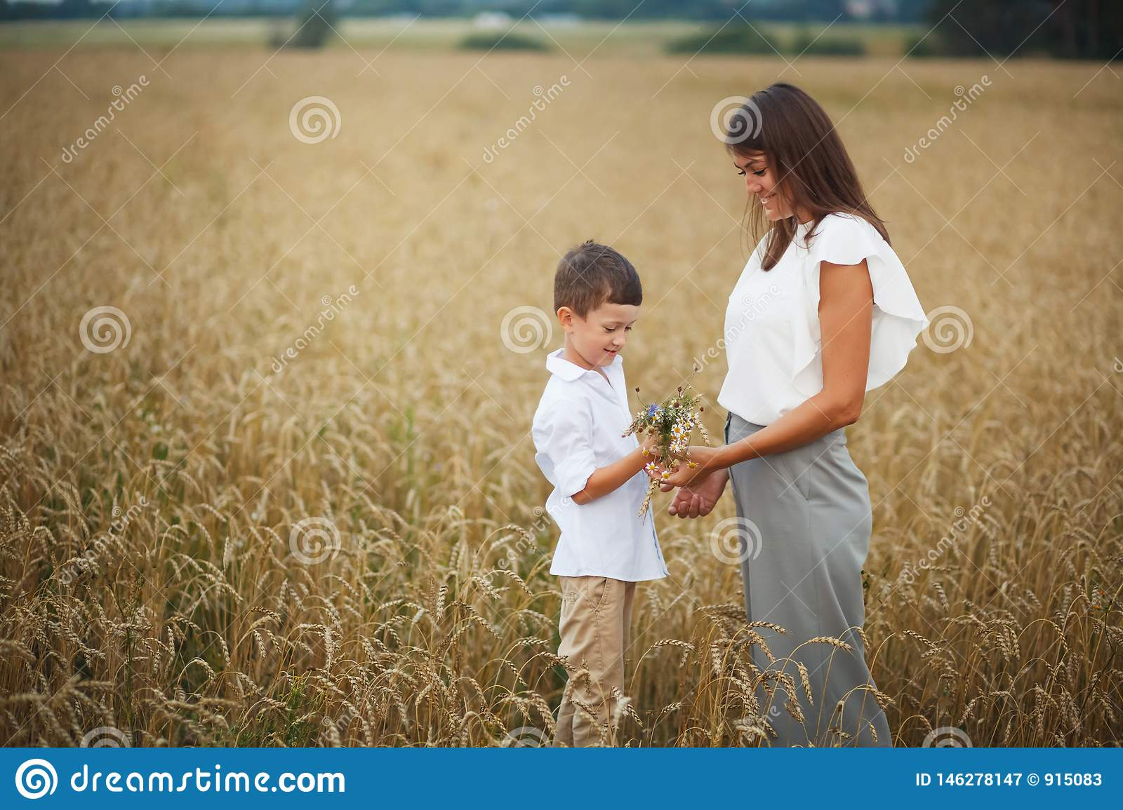 Mother with son smiling holding hands and embracing in a field in summer. The concept of maternal love and tenderness, the