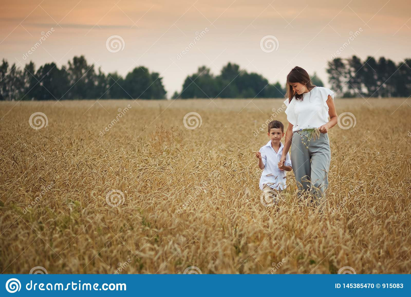 Mother with son smiling holding hands in a field in summer. The concept of maternal love and tenderness, the relationship between