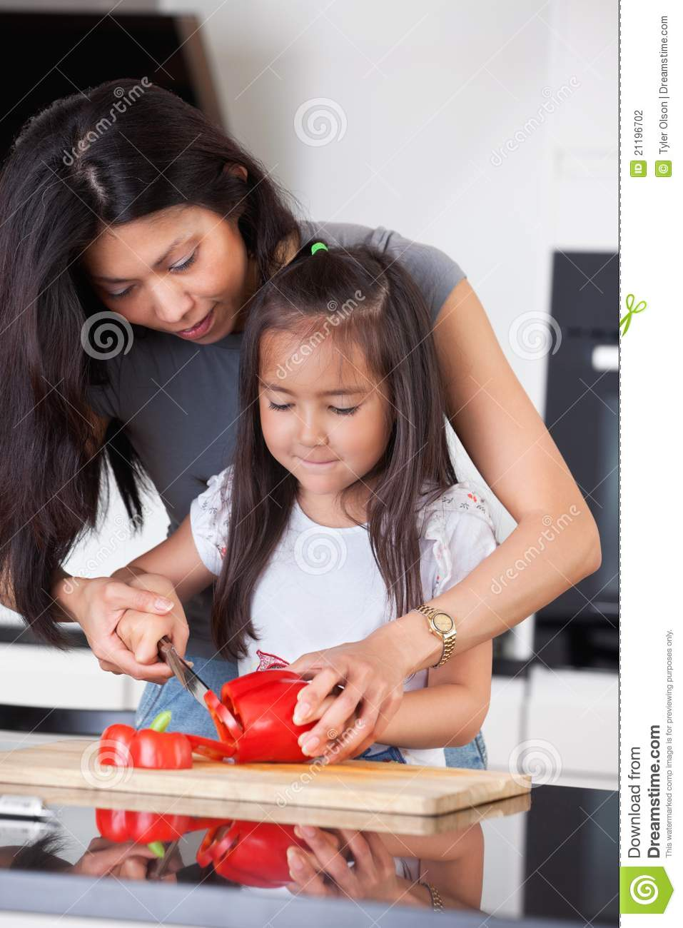 Mother teaches daughter to cook