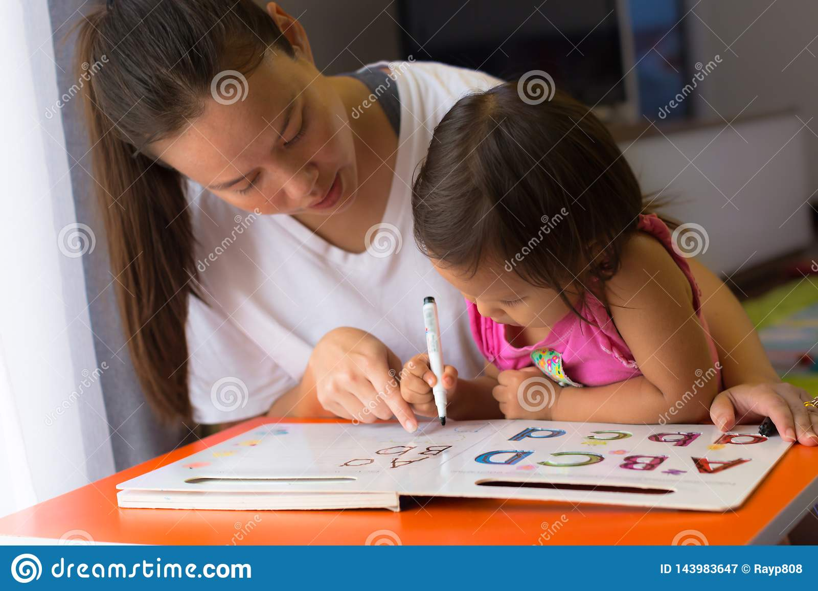 A mother teaching her child how to write the alphabets. homeschooling concept. Kids focusing and concentrating