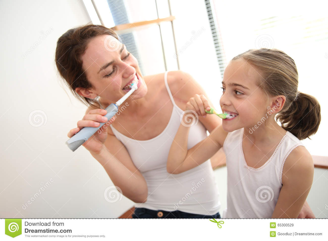 Mother teaching her daughter how to brush teeth