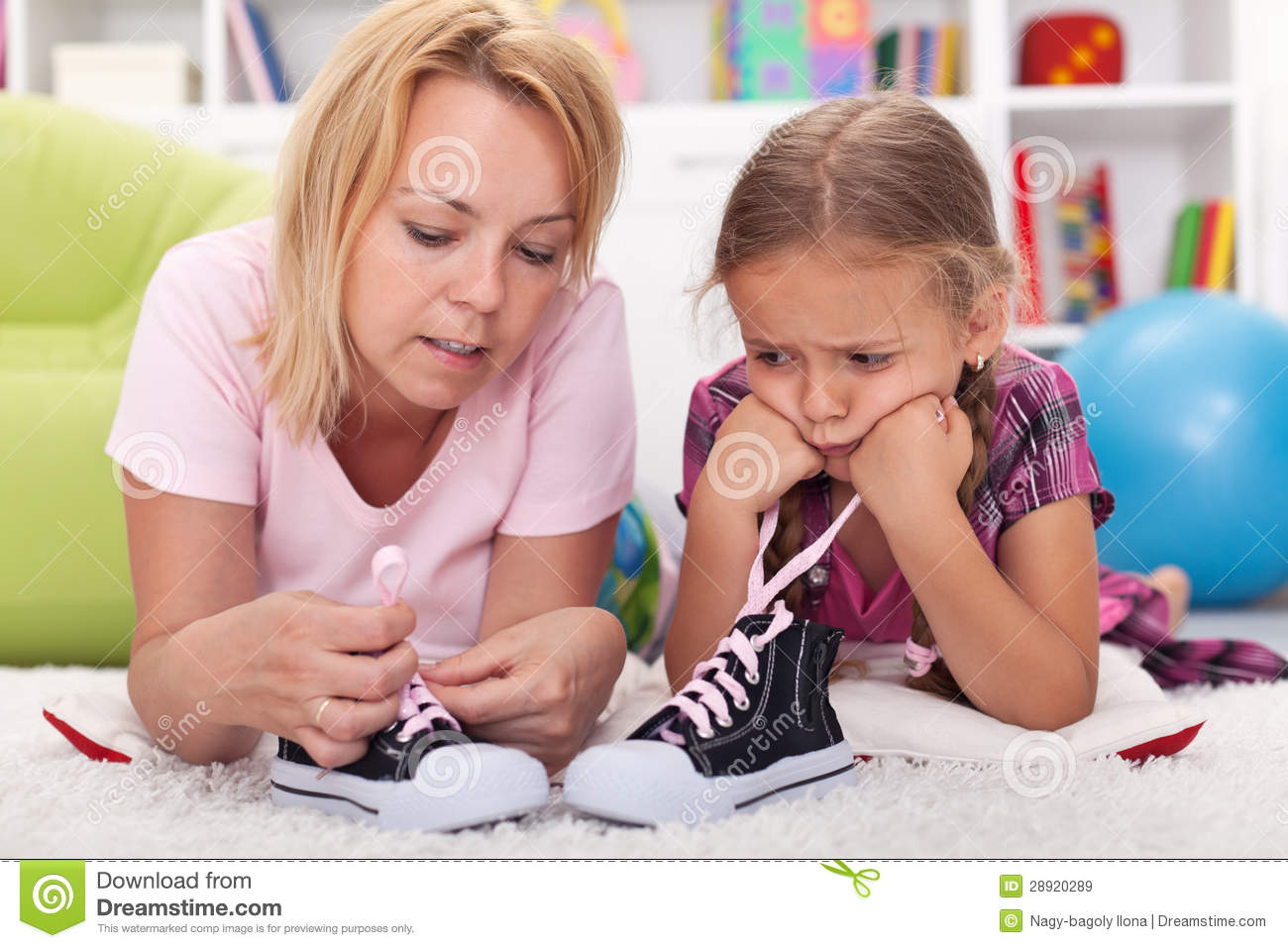 Mother teaching little unhappy girl to tie her shoes showing the