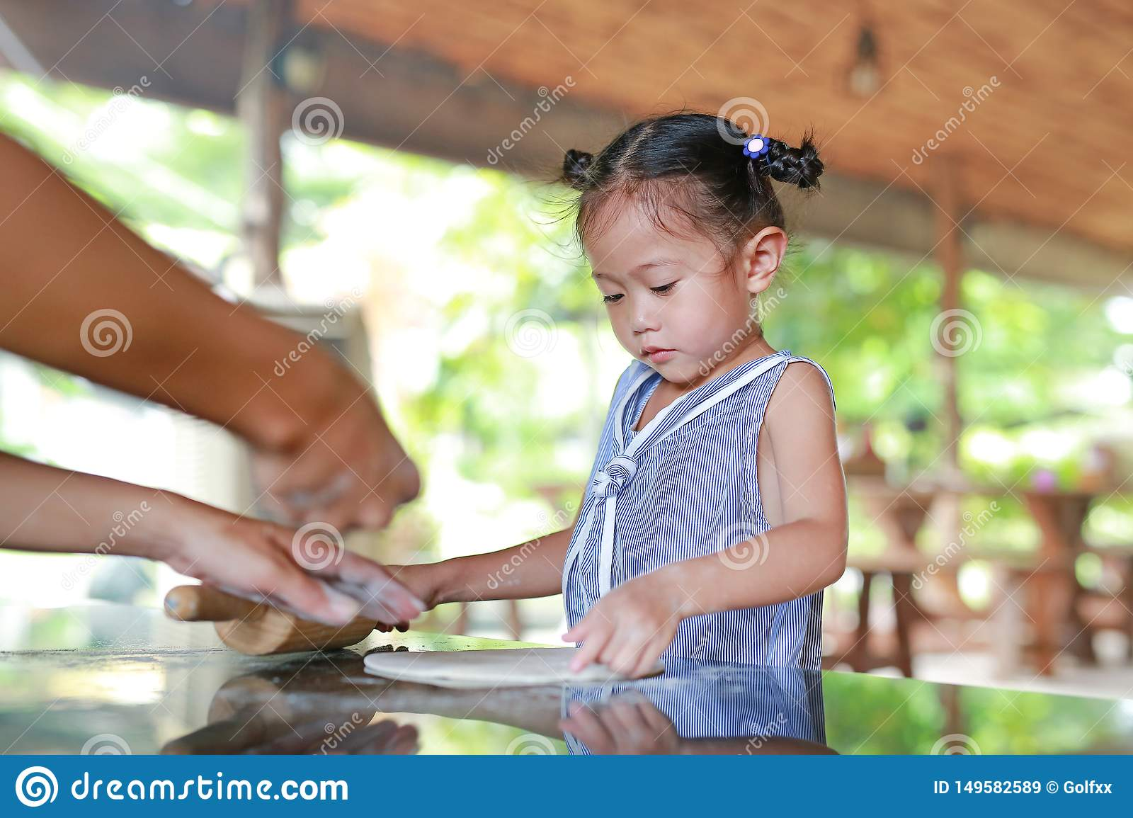 Mother teaching little girl for using Wooden rolling pin on Dough for pizza