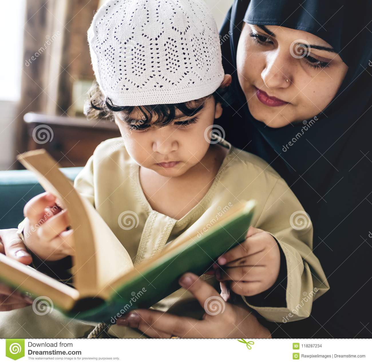 Mother teaching son to read Quran