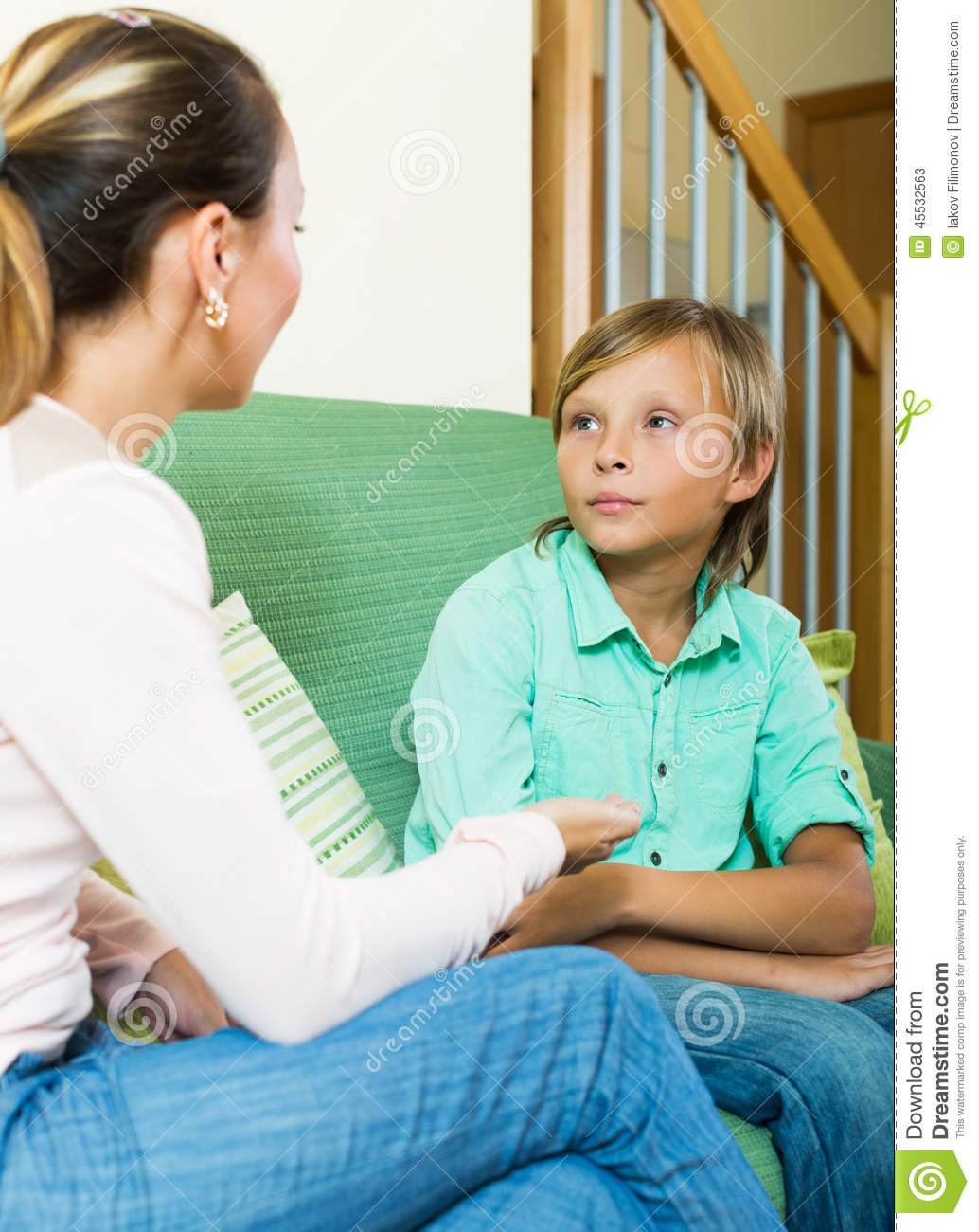 Mother and teen boy talking in home