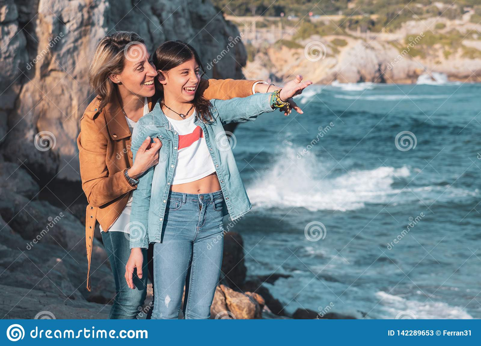 Mother and teenage daughter laughing and pointing to something in the Mediterranean Sea