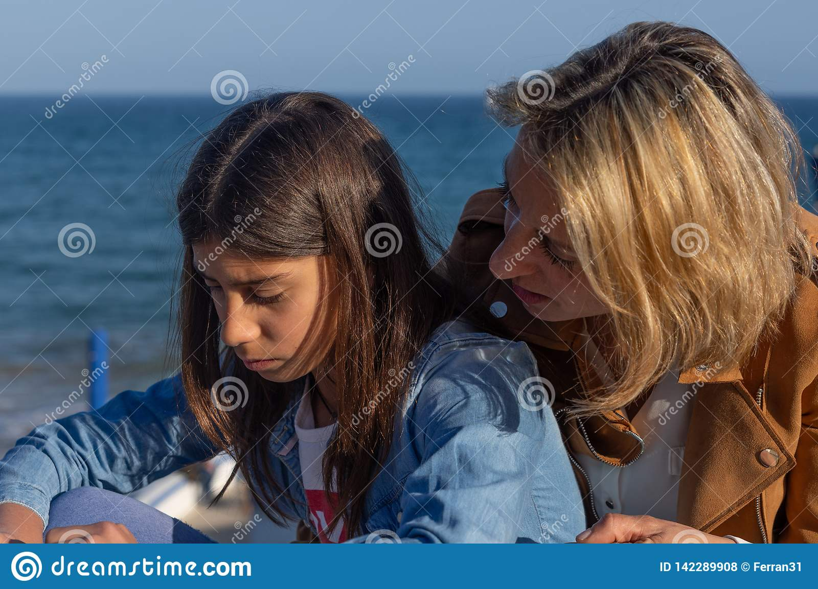 Mother and teenage daughter talking by the mediterranean sea