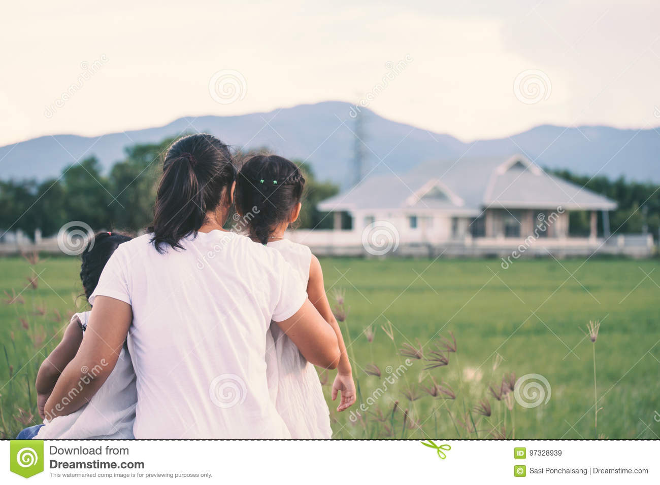Mother and two asian little child girls looking at house