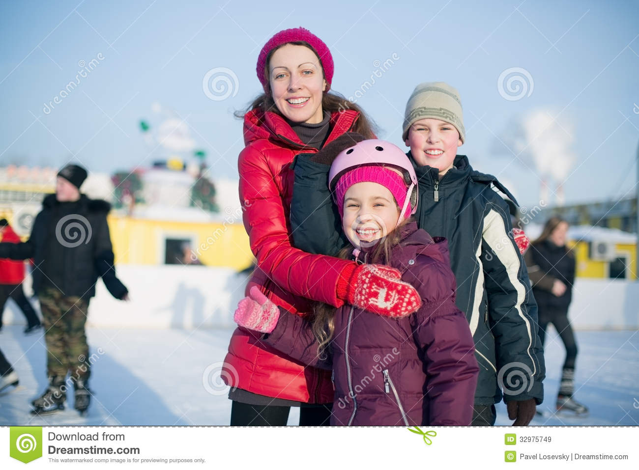 A mother with two children standing on the outdoor rink