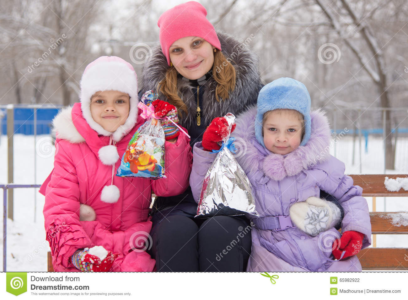 Mother and two daughters with Christmas gifts in his hands