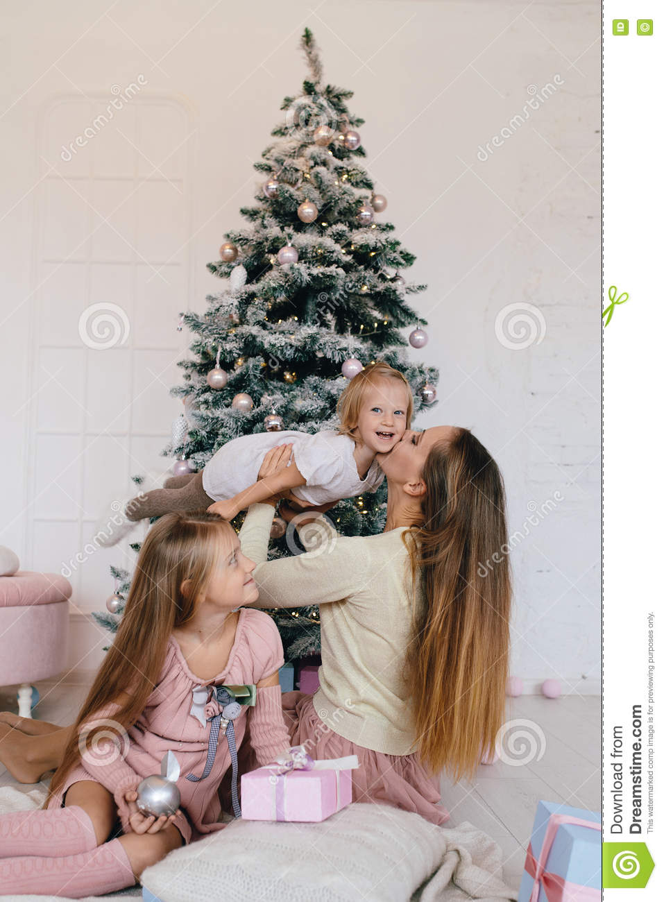 Mother and two daughters playing at at home near Christmas tree. happy family have fun for the Christmas holidays