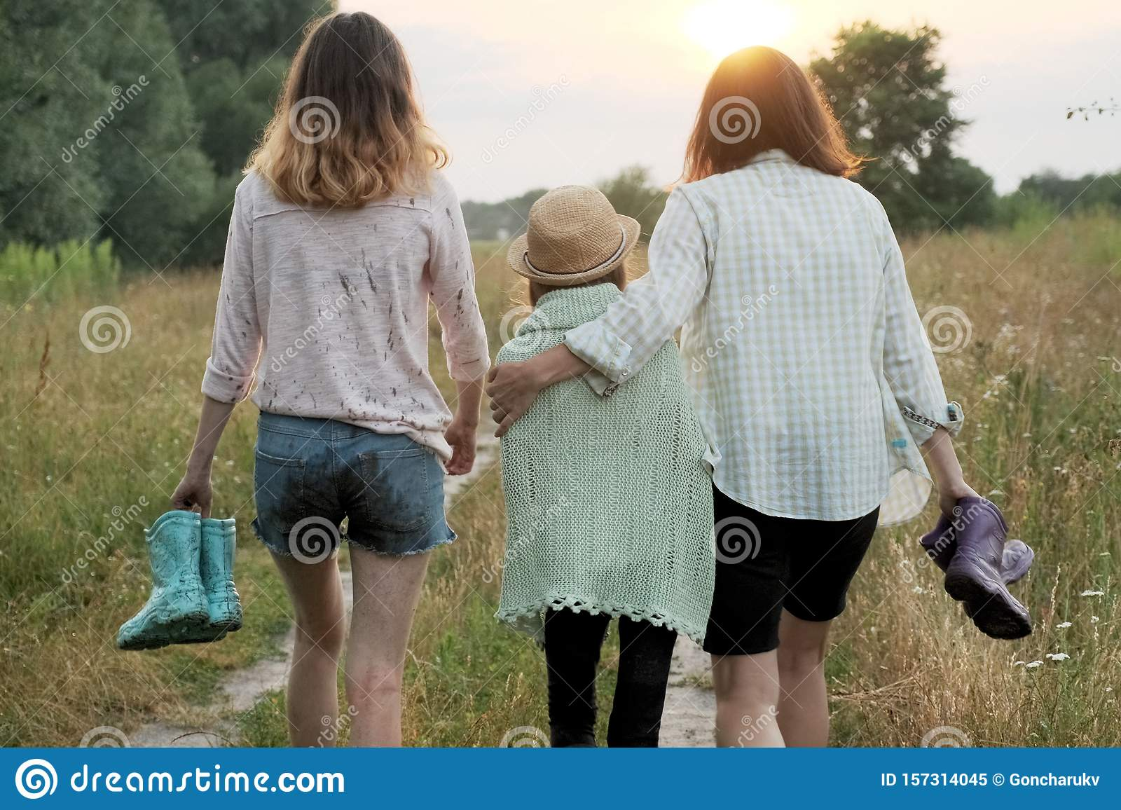 Mother and two daughters walking together along country road