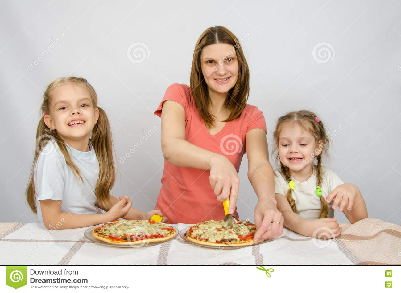 Mother and two little daughters happy sitting at pizzas