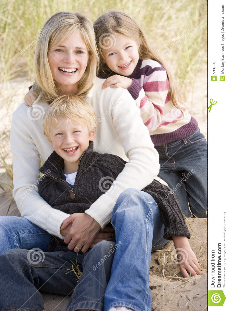 Mother and two young children sitting on beach
