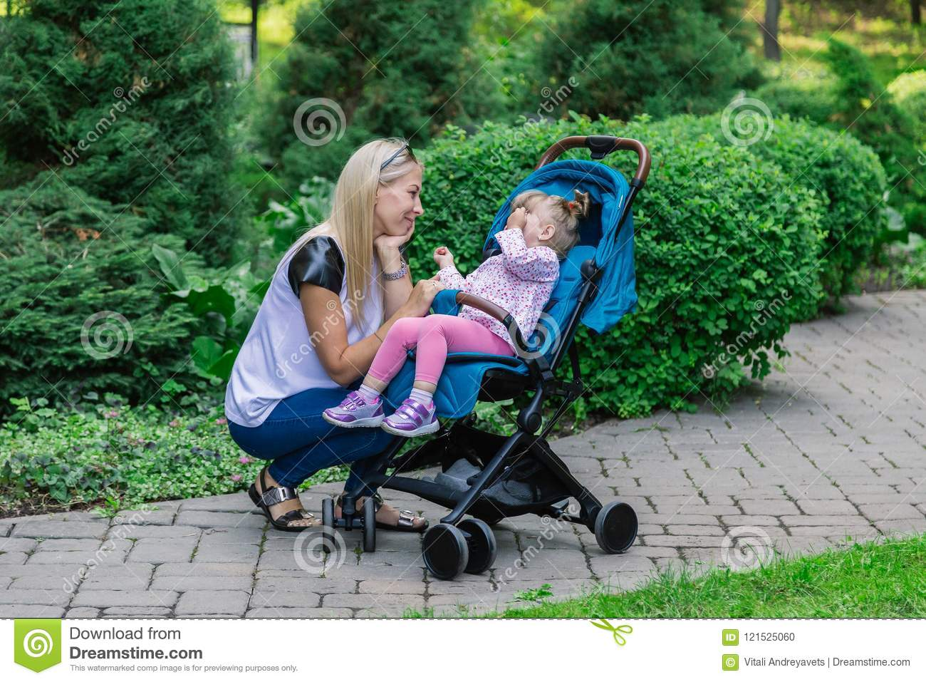 f25ec726dff5 Mother Walking While Pushing A Stroller In The Park Stock Photo ...