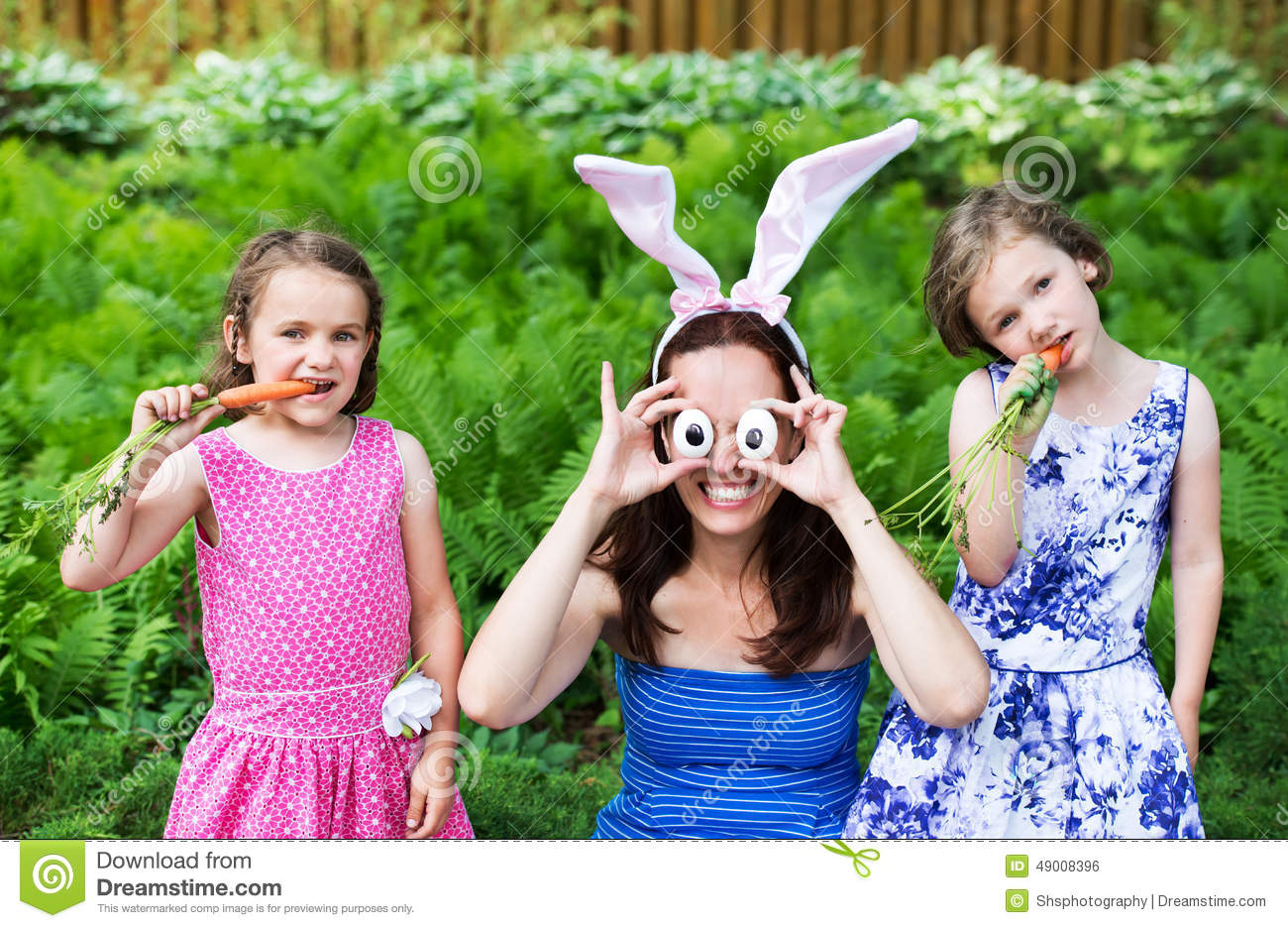 Download Mother Wearing Bunny Ears And Silly Eyes Poses With Children Stock Photo