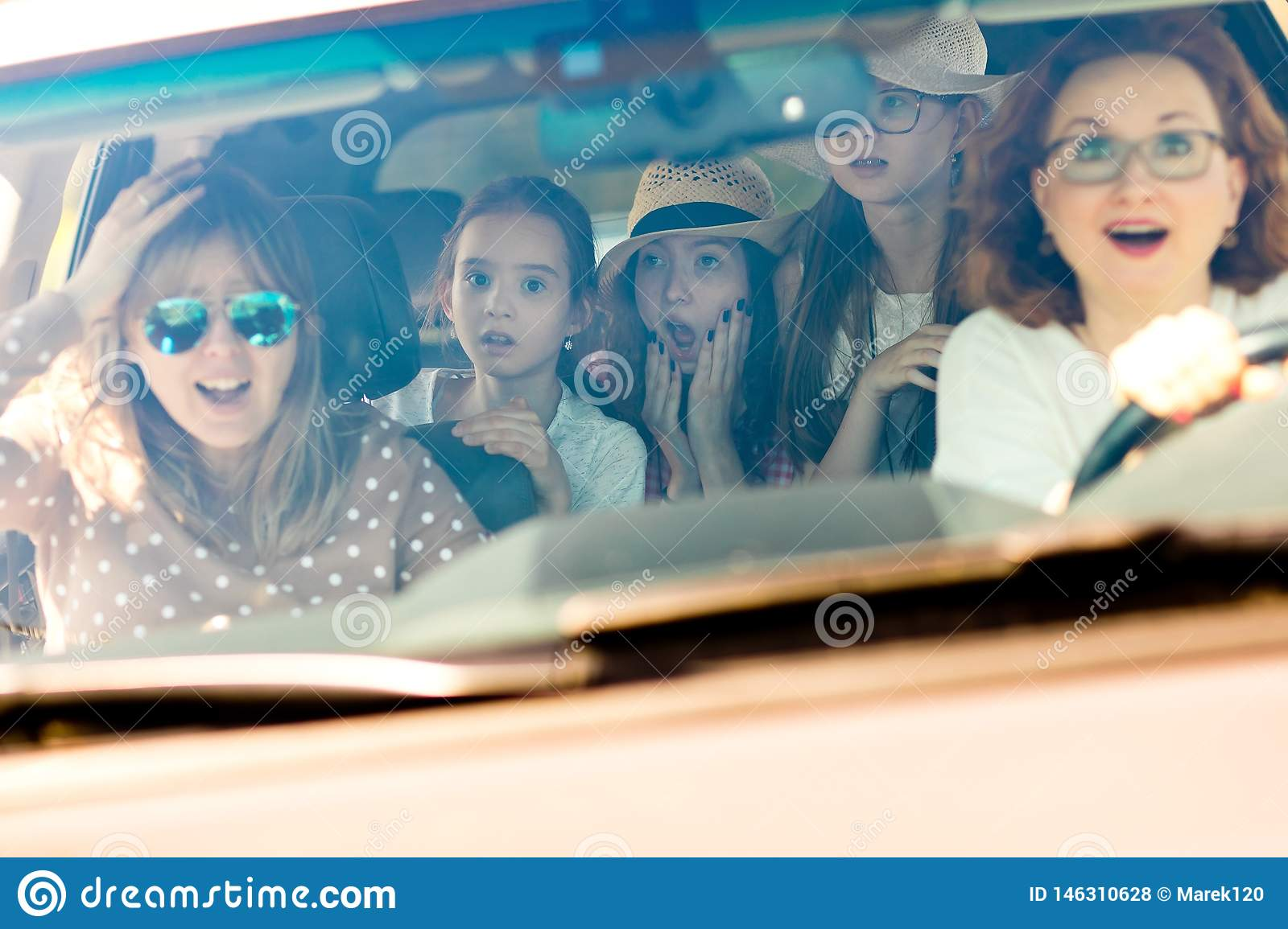 Mothers with daughters scared in car - looking amazed by incoming accident