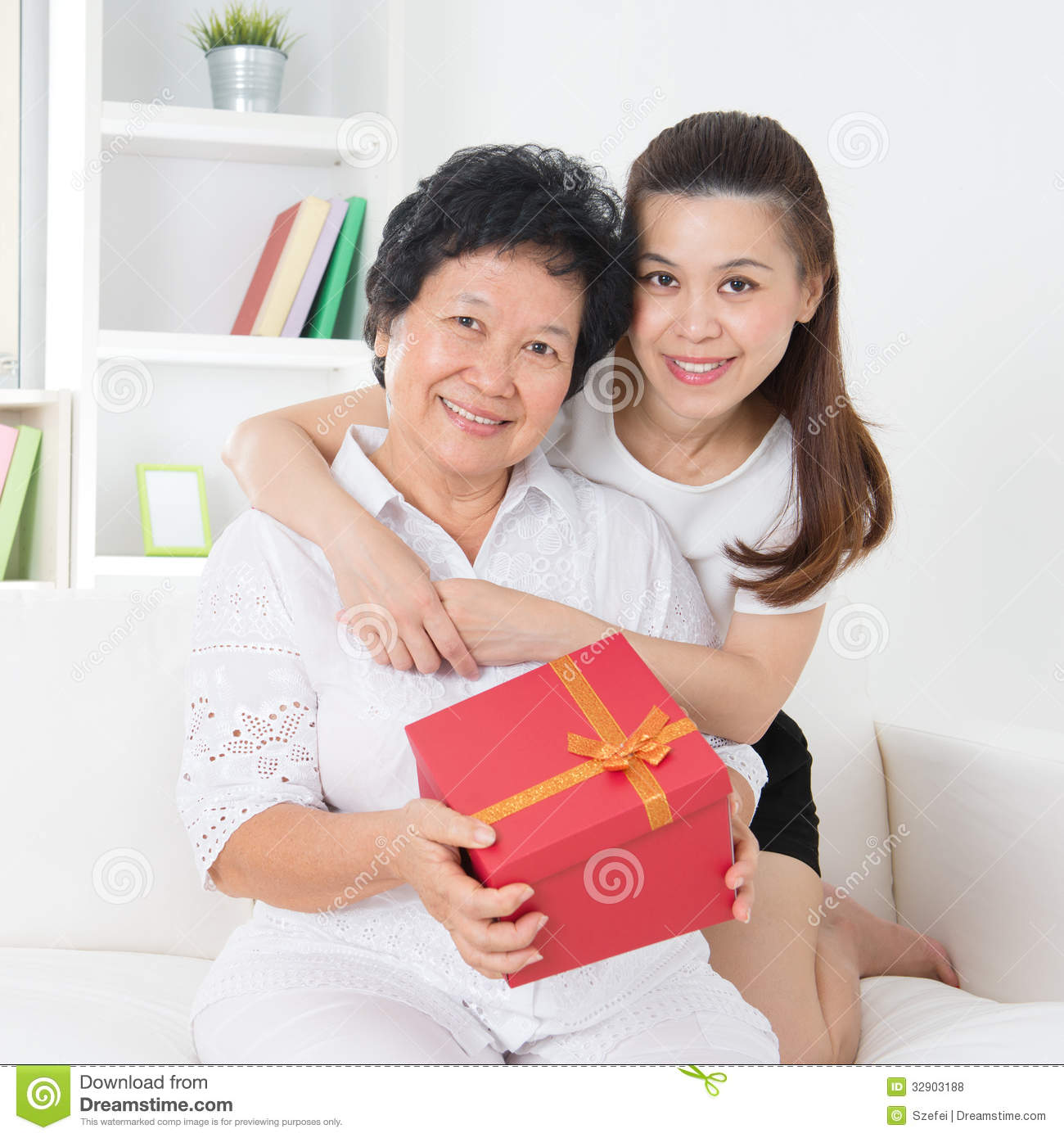 Senior women receiving a gift from adult daughter, beautiful Asian ...