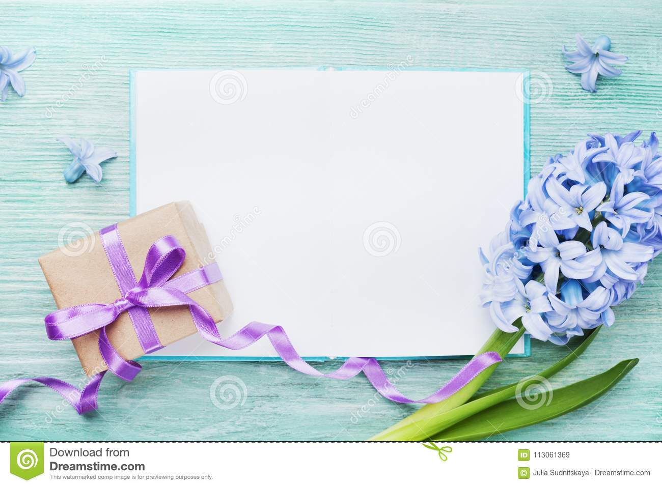 Mothers Day holiday card with empty notebook for greeting text, gift or present box and fresh flowers top view.