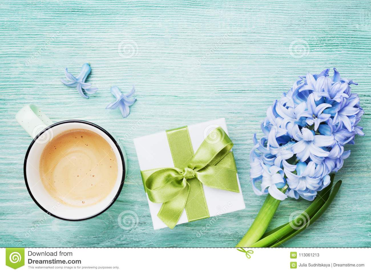 Mothers Day spring greeting background with flowers, gift or present box and cup of coffee top view. Morning breakfast for holiday