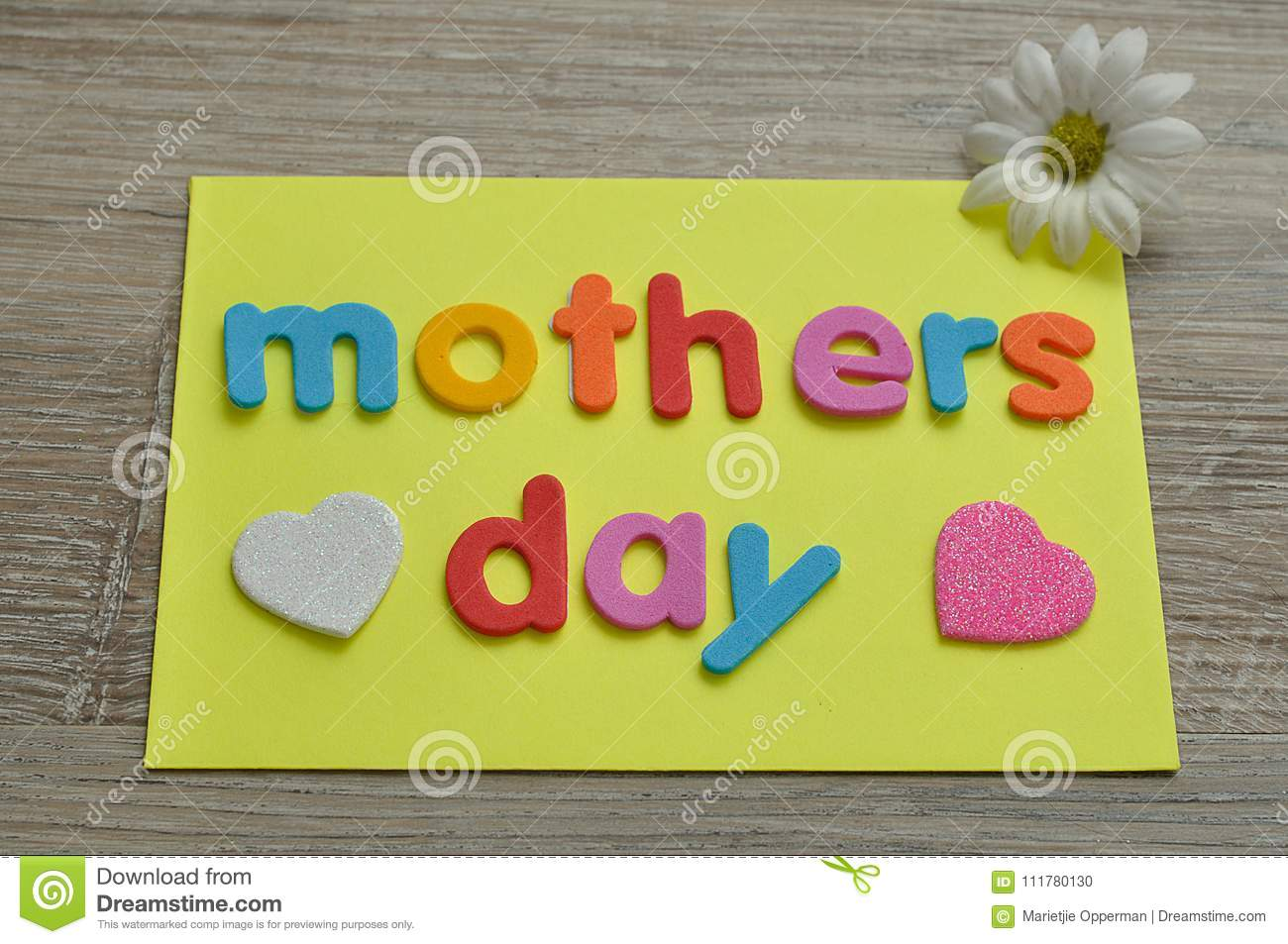 Mothers day on a yellow note with a white and a pink heart and a white daisy