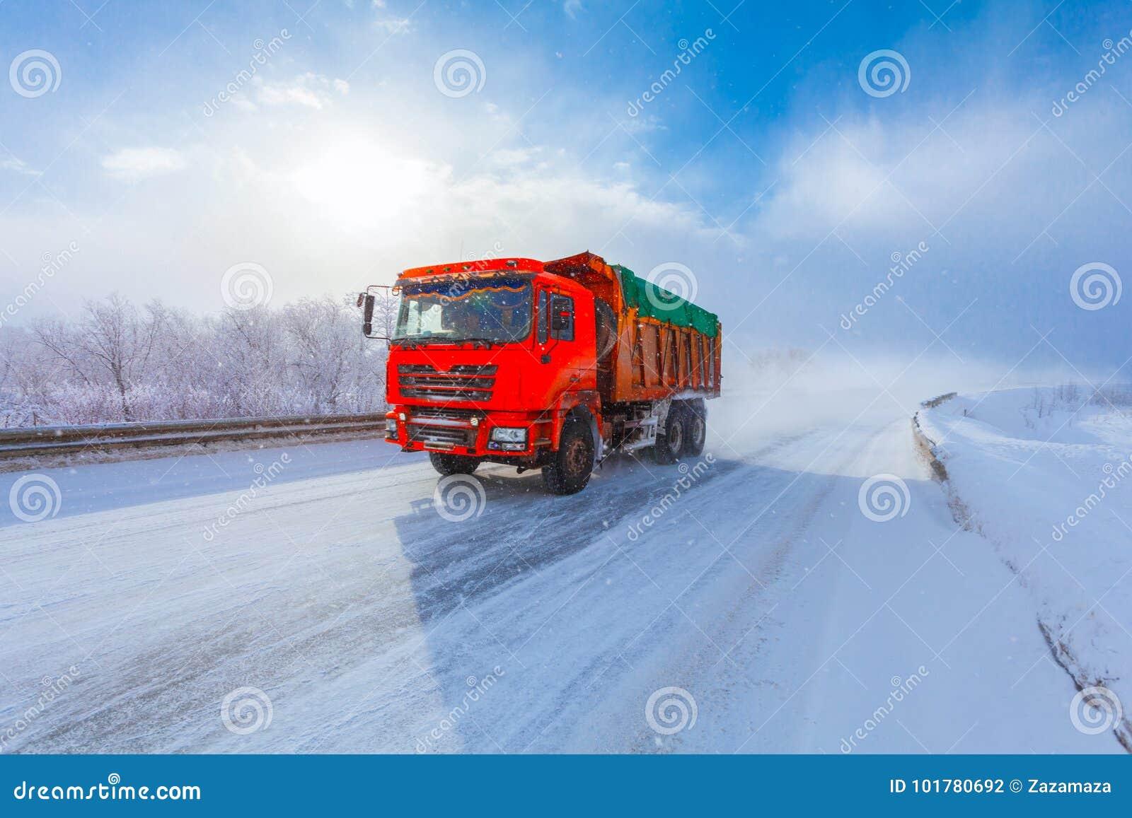 Motieonduidelijk beeld van een rode stortplaatsvrachtwagen met lading op de winterweg