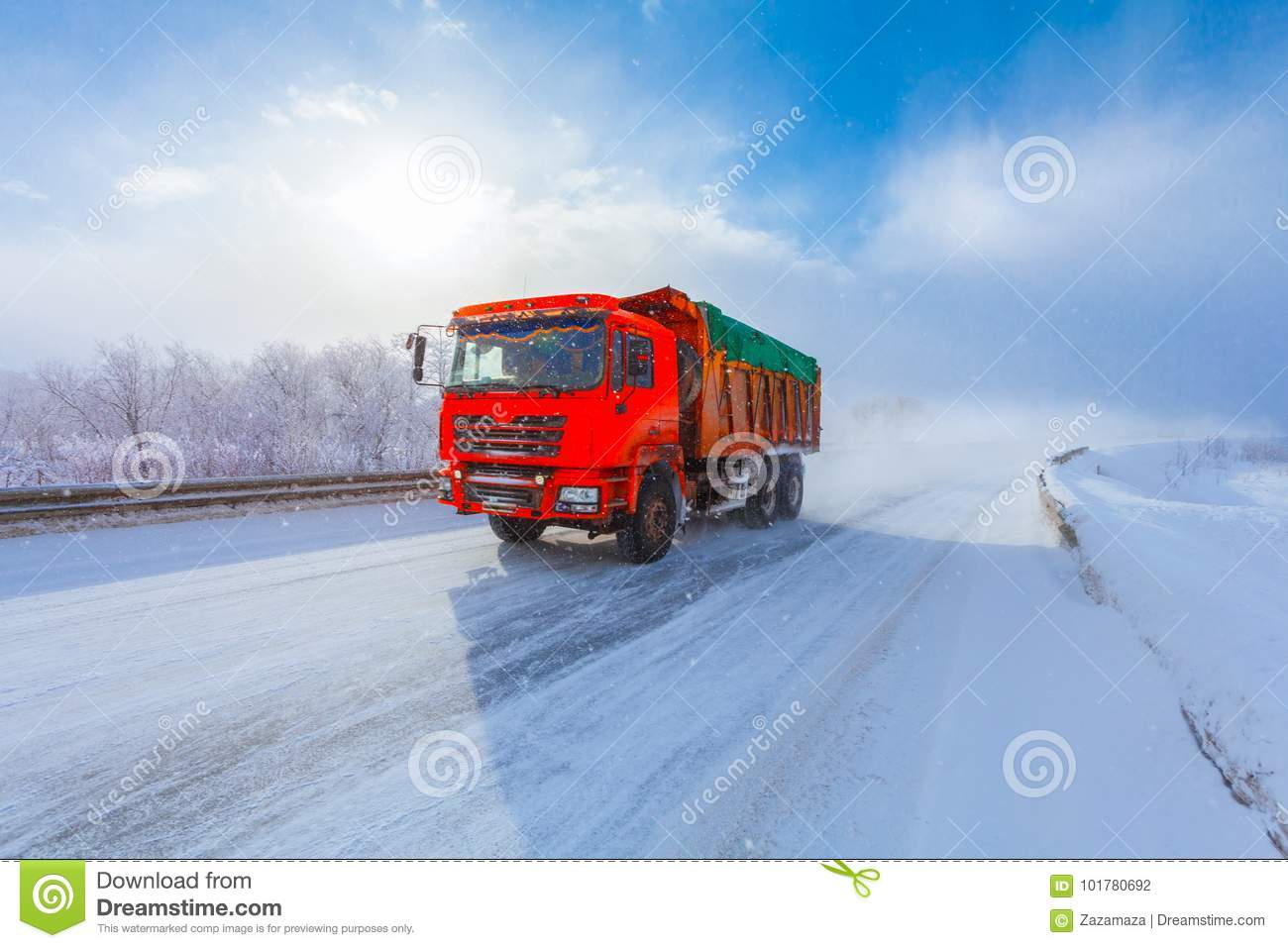 Motion blur of a red dump truck with cargo on winter road.