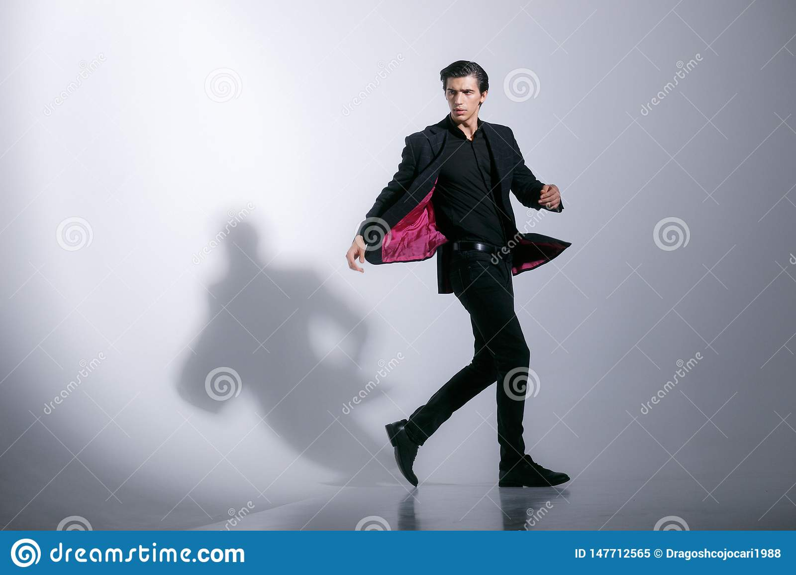 Motion image of a attractive strong young man in full elegant black suit isolated on